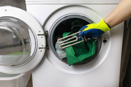 washing machine breakdown. The master retrieves the floor part. In the hands of a spiral and adjustable spanner. Close-up.