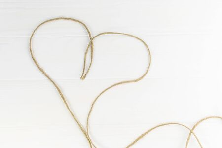 gray rope lies in the shape of a heart. Wooden background in white.