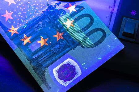 100 Euro banknote. Lying in the ultraviolet to verify the authenticity of banknotes. Close-up.