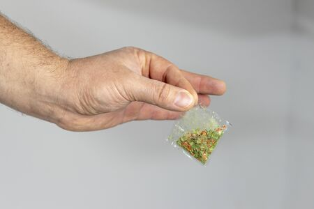 Human grass. In the hand is a bag with a prohibited substance. Close-up. On a gray wall background Stock fotó
