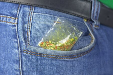 Blue jeans. A hand takes a bag of pickled material from his pocket. Close-up Stock fotó