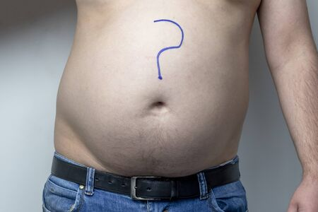 man shakes creases on his stomach. Close-up. On white background