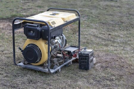 close-up. Street lighting. A gasoline-powered generator that produces current. A car battery is connected for charging. Backup or emergency power source. The generator is not new. Stock fotó