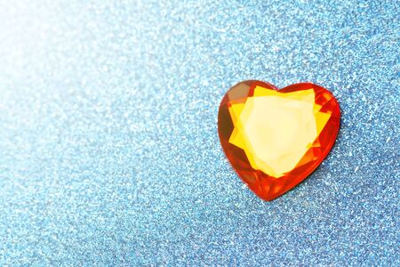 blue background with sparkles with shallow depth of field. Soft focus. Red heart. copy space
