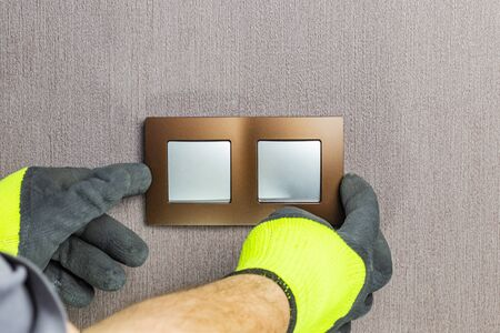 the master electrician sets the switch. Close-up. The room is colored. The switch is brown. The keys are silver. There is a tint.