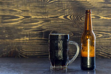fondo in legno, boccale e bottiglia di birra scura con schiuma. Copia spazio. Avvicinamento