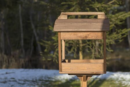 A wooden bird feeder in a dark forest stands on the ground. Shallow depth of field. There is a tint.