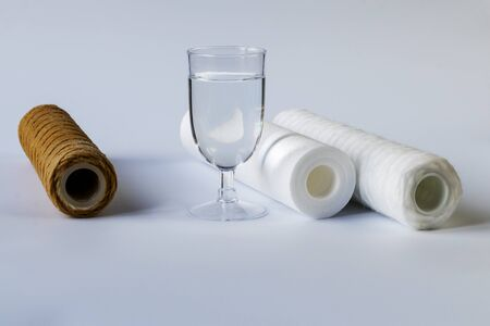 The water filter is two units and a cartridge that requires replacement. Near a glass of clean water. White background, no isolation. Close-up. Stock Photo