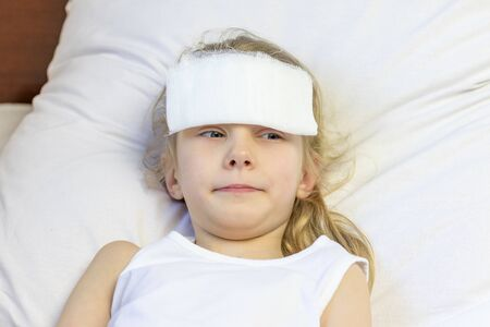 A girl with white hair lies in bed. She has a bandage on her forehead to relieve pain. Close-up. There is a tint.