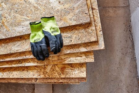 OSB slab building material made from reborn sawdust. They lie in a pile, yellow protective gloves lie on it. Close-up. 写真素材