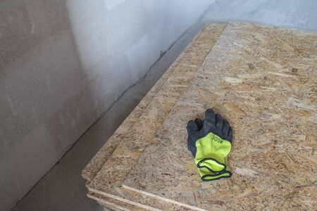 OSB slab building material made from reborn sawdust. They lie in a pile, yellow protective gloves lie on it. Close-up. Фото со стока