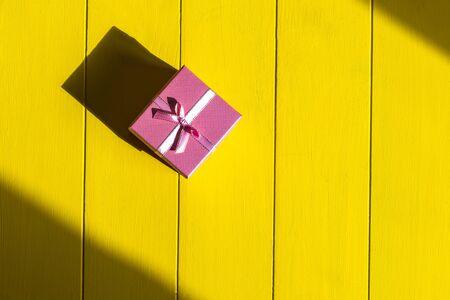 Rough shadow. Retro yellow wooden background. Gift box in pink. Standard-Bild