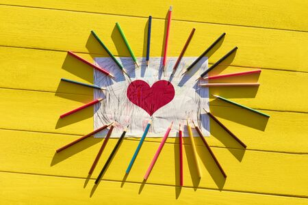 Rough shadow. Bright sunshine. Retro yellow wooden background. In the center, a sheet of paper with drawings and around lined with pencils of different colors. There is a painted red heart Standard-Bild