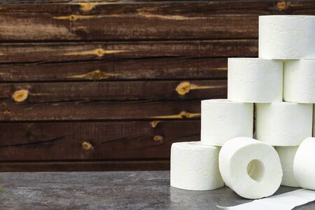 wooden background in retro style on it lined with pyrimide toilet paper.