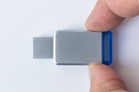 USB Flash White background. There is a metal flash on it. Close-up. The cap is missing.