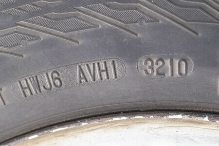 stamping on a tire where date and year of issue are indicated. Close-up. Old wheel, replacement required.