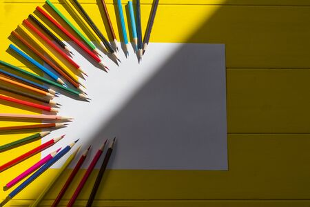 Rough shadow. Bright sunshine. Retro yellow wooden background. In the center, a sheet of paper with drawings and around lined with pencils of different colors