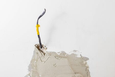Plastered white wall. It displays a cable for connecting outlets. Copy space. Close-up