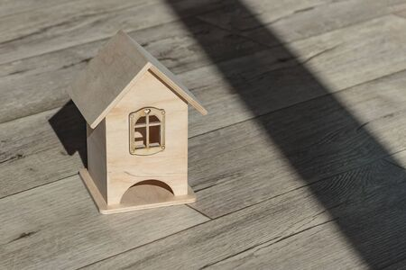 Mock up little wooden house. Bright shadows casts on the background. Close-up. There is a tint. Standard-Bild