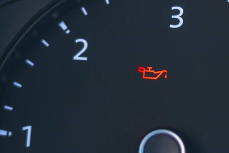The automobile tachometer has a low oil indicator on it.