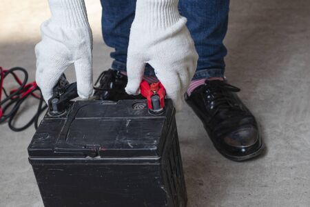 on the concrete floor a flock of car battery, the master puts clips on the terminals for recharging