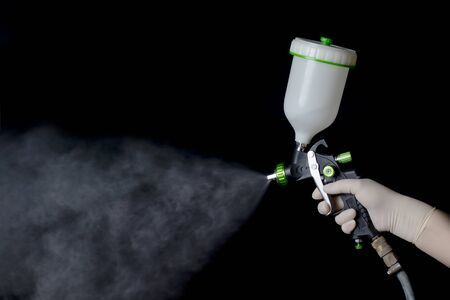 a hand in a rubber glove holds a mechanical atomizer. Holds the trigger, he sprays. Black background.