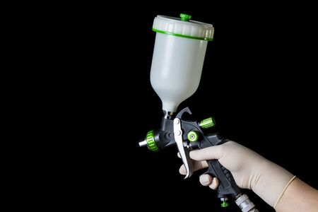 a hand in a rubber glove holds a mechanical atomizer. Black background.