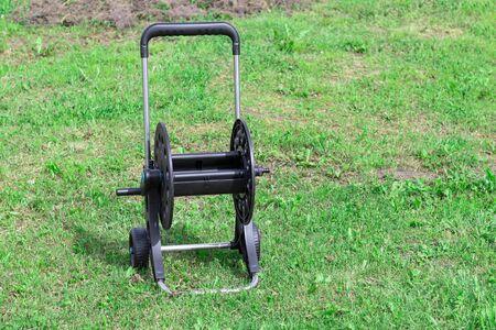 daylight. on the grass is a hose cart. close-up. Standard-Bild