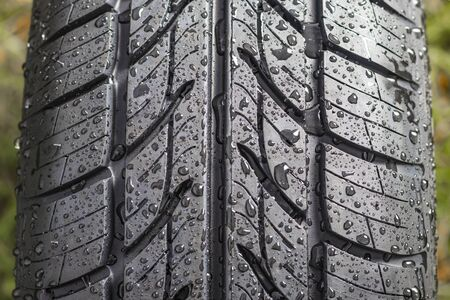 New tire. There are raindrops on it. The tread pattern is looking at us. Close-up