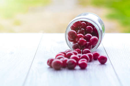 Fresh collected red cherry in a glass jar. Berries are scattered on a wooden background.