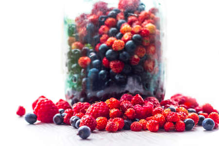 On a white background. Glass jar. Freshly picked blueberries, raspberries and wild strawberries