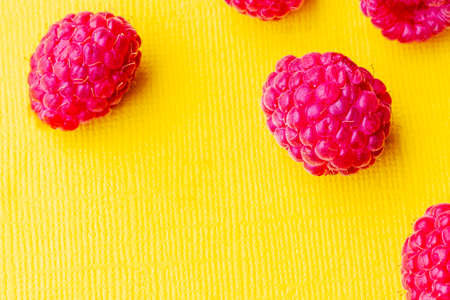 yellow background. On it is a red berry raspberry. Close-up