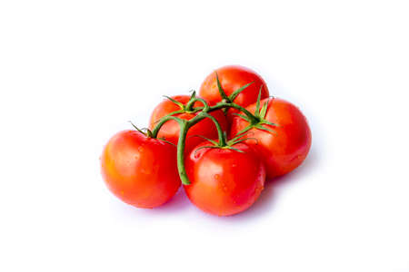 On a white background. No isolation. Red tomato on a green branch. There is a shadow Stock Photo