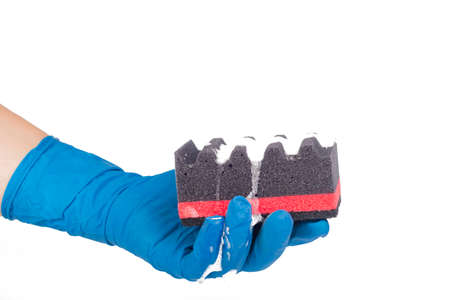 A man's hand in a blue household glove holds a corrugated black sponge, dishwashing detergent is applied. On white background. Close-up. Banque d'images