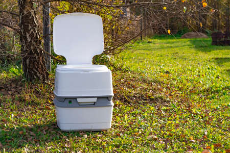 Street lighting. a portable plastic toilet in the foreground. In the back there is a tree Standard-Bild