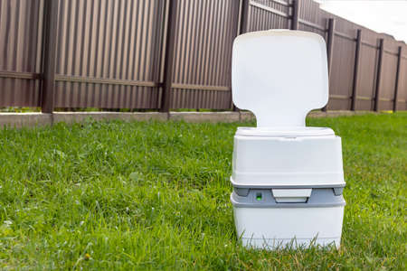 Street lighting. a portable plastic toilet in the foreground. In the background is a dark metal fence