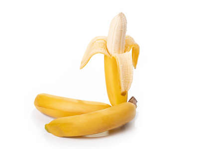 Shooting in the studio. A branch of ripe yellow bananas in a peel. On white background. Close-up