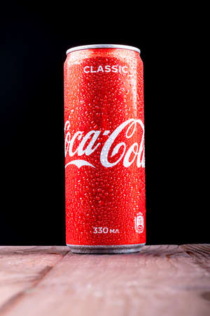 Minsk. Belarus. October 23, 2020. Studio lighting. A red metal can of Coca-Cola is covered with crayons of water. Chilled. Stands on a wooden background in a retro stele