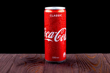 Minsk. Belarus. October 23, 2020. Studio lighting. A red metal can of Coca-Cola is covered with crayons of water. Chilled. Stands on a wooden background in a retro stele.