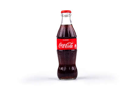 Minsk. Belarus. October 23, 2020. Studio lighting. red glass jar of Coca-Cola covered with water droplets. Chilled. On white background