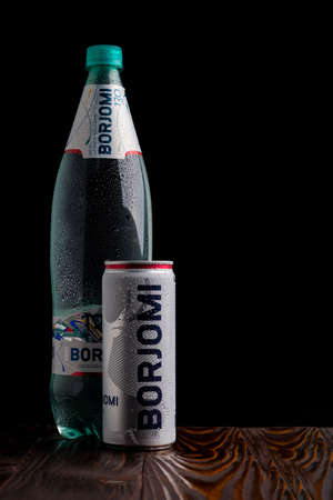 Minsk. Belarus. October 24, 2020 studio lighting. on a wooden background in a retro stele there is a metal can with water drops on it. Black background. borjomi. Editoriali