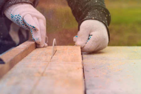 Daylight. machine for sawing wood. The master hands the board. Close-up Archivio Fotografico