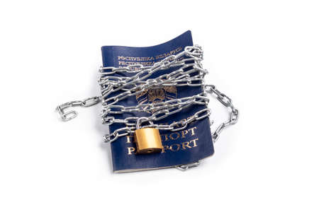 Studio lighting. the citizen's passport is tied with a metal chain in the center with a yellow lock. The concept of violation of the rights of citizens, a ban on movement. Archivio Fotografico
