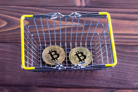 studio lighting. wooden background in retro style. There are two bitcoin in the metal basket