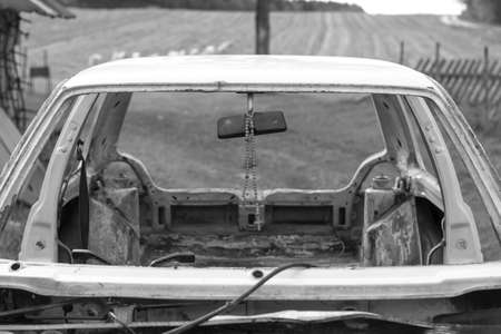 daylight. unassembled white car. There is a wooden cross in the center of the frame. The concept is a consequence of carelessness on the road.