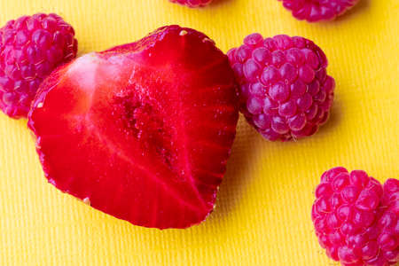 Yellow background. It has red strawberries, it is cut in half and next to it is raspberry. Close-up.