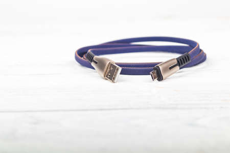 Studio lighting. usb wire for connecting to a computer in blue or purple on a wooden white background in retro style. Close-up.