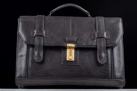 studio lighting. black leather, suitcase, bag, briefcase. On a wooden background. The background is dark. Close-up
