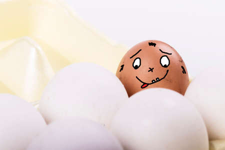 Studio lighting. a tray of white eggs about one brown. It has a picture in the shape of a face Фото со стока