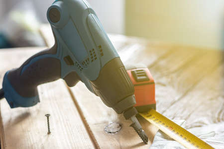 studio lighting. electric impact screwdriver. Wooden background in retro style. Soft focus. Close-up